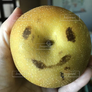 近くに果物を持っている手のアップの写真・画像素材[1407778]