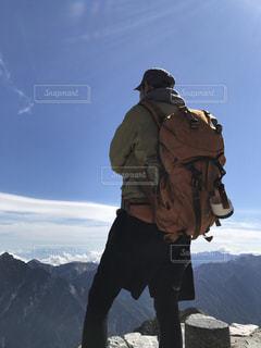 雪に覆われた山の頂上に立っている男の写真・画像素材[1697262]