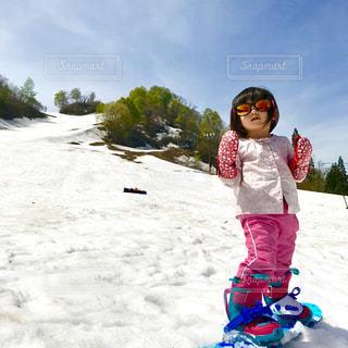 雪に覆われた斜面の上に乗る少女の写真・画像素材[1737749]