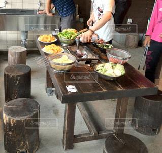 木製テーブルの上に食べ物を準備する人の写真・画像素材[1245966]