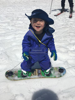 小さな子供は雪の中に座っています。の写真・画像素材[1295263]