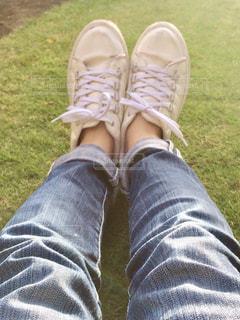 白い靴とジーパンと芝生の写真・画像素材[1256038]