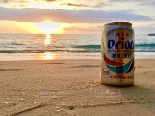 夕陽と海とオリオンビールの写真・画像素材[1385155]