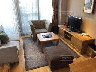 部屋にコンピュータと椅子が付いた机の写真・画像素材[2948211]