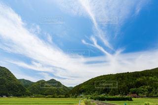 背景の山に大規模なグリーン フィールドの写真・画像素材[1254237]