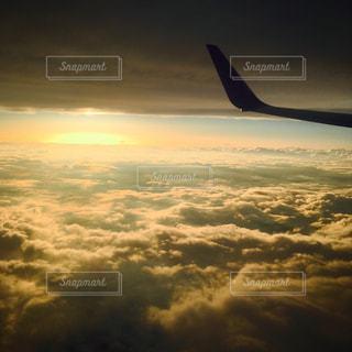 飛行機,夕陽,雲の上から