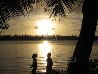 子ども,2人,自然,空,太陽,ビーチ,夕焼け,夕暮れ,水面,海岸,女の子,光,旅行,ヤシの木