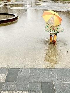 イエローな子供と水溜りの写真・画像素材[3673714]
