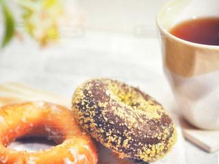 近くのコーヒー カップの横に座っているドーナツのアップの写真・画像素材[1884918]
