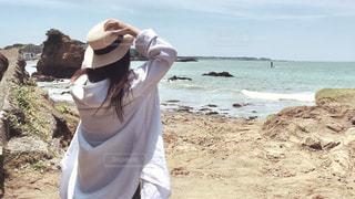 岩の多い浜辺に立つ女性の写真・画像素材[2260151]