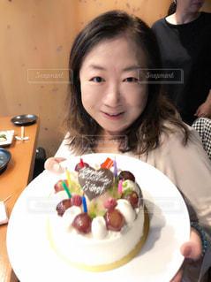 皿の上のケーキをテーブルに着席した人の写真・画像素材[1668560]