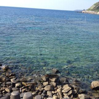 水の体の横にある岩のビーチの写真・画像素材[1395800]