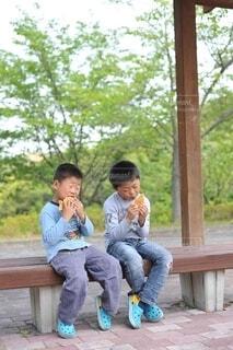 ベンチに座ってたい焼きを食べる兄弟の写真・画像素材[4101213]