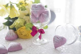 花束と、ワイングラスに入ったハートのひと粒チョコレートの写真・画像素材[4156606]