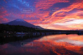 背景の山が付いている水の体に沈む夕日の写真・画像素材[1269128]