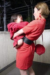 赤いシャツを持った小さな女の子の写真・画像素材[2174028]