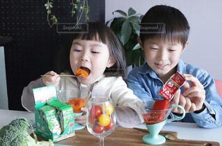 食べ物を食べるテーブルに座っている小さな男の子の写真・画像素材[4261604]