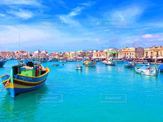 満ちている水の体の青と黄色のボート港の写真・画像素材[1316733]