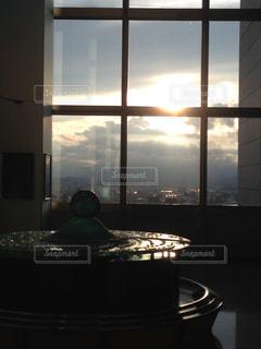 窓の前のテーブルに座っている人の写真・画像素材[1280187]