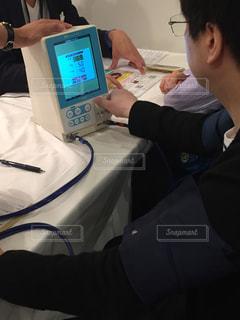 血圧を測っている座っている若い男の写真・画像素材[1326228]
