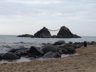夫婦岩を眺むカップルの写真・画像素材[1426132]