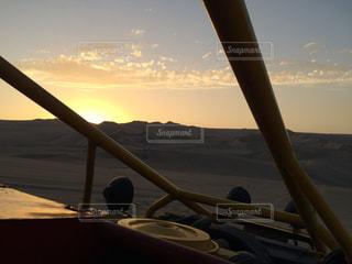 砂漠とバギーと夕日の写真・画像素材[1292020]