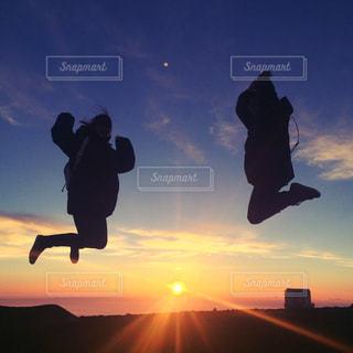 背景の夕日と、空気中のジャンプ人の写真・画像素材[1283969]