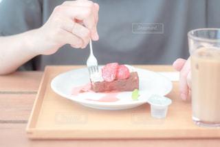 テーブルの上にコーヒーを1杯持っている人のクローズアップの写真・画像素材[2293446]