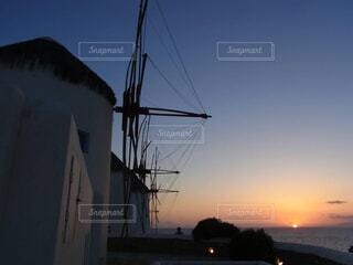 エーゲ海に沈む夕陽と風車の風景の写真・画像素材[4457412]