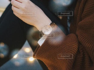ブラウンの時計をつけてる女性の手元の写真・画像素材[3793958]