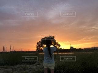背景の夕日と草の中に立っている男の人の写真・画像素材[1292837]