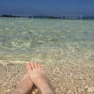 水の体の近くのビーチに座っている男の写真・画像素材[1312659]