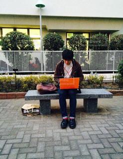 建物の前にあるベンチに座っている人の写真・画像素材[1295130]