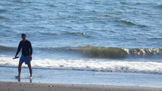 海の隣のビーチを歩いている人の写真・画像素材[4608989]