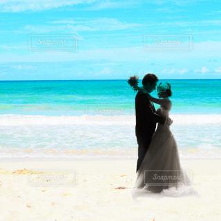 海の横にある砂浜のビーチの上に立っている人の写真・画像素材[1314318]