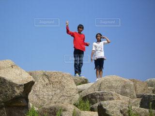 岩が多い丘の上に立っている人の写真・画像素材[1316857]