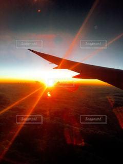オレンジ色の夕日に大きい飛行機の写真・画像素材[1298441]