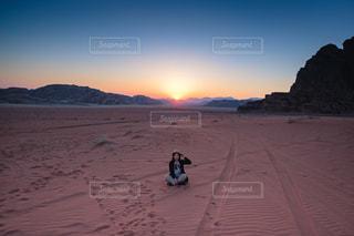 女性,風景,夕日,絶景,景色,日没,観光,人物,逆光,人,砂漠,ポートレート,海外旅行,ヨルダン,あぐら,若い女性,ワディ ・ラム,中折れ帽