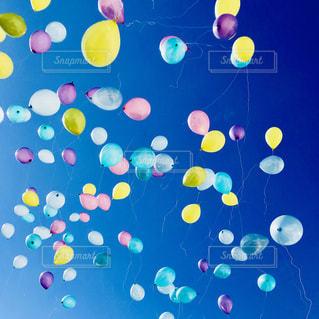 青空に飛び立つ色とりどりの風船の写真・画像素材[1312714]