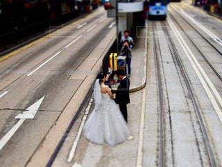 列車レールの真ん中でウェディングフォトを撮るカップルの写真・画像素材[1324229]