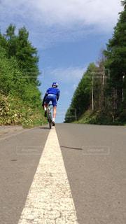 未舗装の道路を自転車に乗る人の写真・画像素材[1309712]