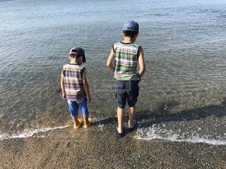 水の体の横に立っている少年の写真・画像素材[1391490]