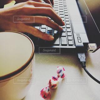 テーブルの上に座っているラップトップ コンピューターを使用している人の写真・画像素材[1319940]
