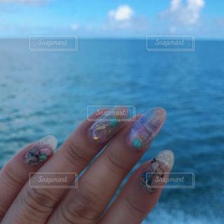 水の体の横に水のボトルを持っている手の写真・画像素材[1326361]