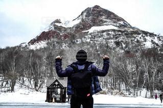 雪に覆われた山の頂上に立っている男の写真・画像素材[1407935]