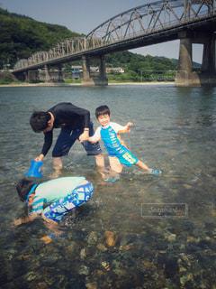 水の体に架かる橋の上にいる人々のグループの写真・画像素材[3639925]