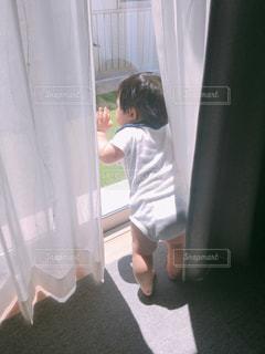 カーテンの前に立っている人の写真・画像素材[2178528]