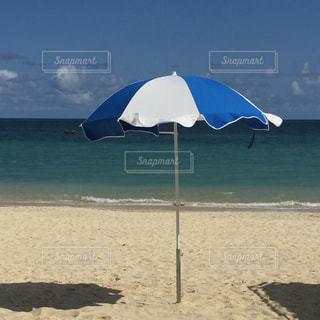 砂浜の上に座って傘の写真・画像素材[1400524]