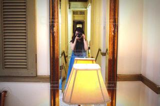 ミラー越しにカメラを構える女性の写真・画像素材[1858721]