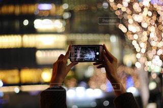 女性,1人,建物,冬,カメラ,きれい,手,スマホ,撮影,光,イルミネーション,人物,人,明るい,玉ボケ,グランフロント,ぼやける